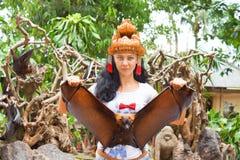 Woman in headdress holding a flying fox Stock Photos