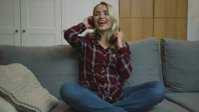 Woman in headphone having fun on sofa stock video footage