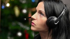 Woman with headphone talking on at the Christmas tree stock footage
