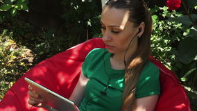 Woman with headphoneand tablet or pad outside stock video