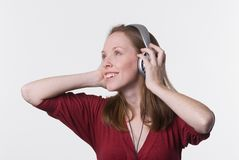 Woman with headphones-01. A young woman joyfully listens to music on headphone while her hands hold the earpieces Royalty Free Stock Photography