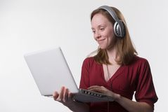 Woman with headphones-02. A smiling young woman wearing headphones listens to music on her laptop computer Stock Photo