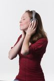 Woman with headphones-07. A young woman joyfully listens to music on headphone while her hands hold the earpieces Royalty Free Stock Photo