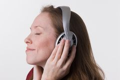 Woman with headphones-08. A young woman joyfully listens to music on headphone while her hands hold the earpieces Stock Image