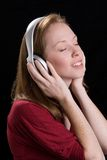 Woman with headphones-10. A young woman joyfully listens to music on headphone while her hands hold the earpieces Stock Image