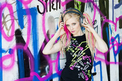 Woman with headphones. Portrait of young woman with headphones at graffitti wall Stock Photography