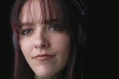 Woman with headphones. Close-up portrait of a young woman wearing headphones.  Woman has a pierced lip and a silver stud in the piercing shot on a black Royalty Free Stock Images