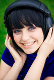 Woman with headphones. Happy young woman listening to music with headphones; green background Royalty Free Stock Images