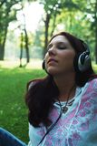 Woman with headphones. Woman listening to headphones outside stock photo