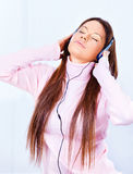 Woman with headphones. Pretty young woman with headphones listening music at home royalty free stock image