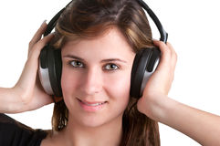 Woman with Headphones. Young woman listening to music through her headphones, isolated in a whiite background Stock Image