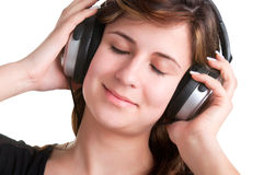 Woman with Headphones. Young woman listening to music through her headphones, with her eyes closed, isolated in a white background Stock Images