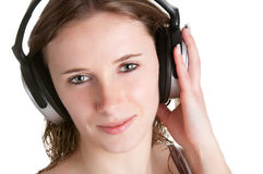 Woman with Headphones. Young woman listening to music through her headphones, isolated in a whiite background Royalty Free Stock Images
