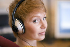 Woman with headphones. Young woman listening to headphones looking directly at camera Stock Photos