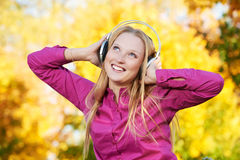 Woman with headphones at autumn outdoors Stock Photos
