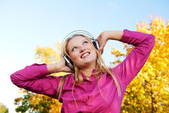 Woman with headphones at autumn outdoors Royalty Free Stock Photography