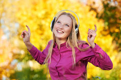 Woman with headphones at autumn outdoors Royalty Free Stock Image