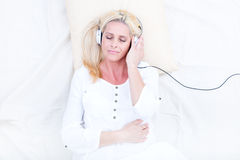 Woman with headphones in Bed Stock Photos