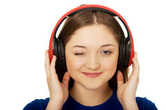 Woman with headphones blinks eye. Royalty Free Stock Photos