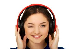 Woman with headphones blinks eye. Royalty Free Stock Photo