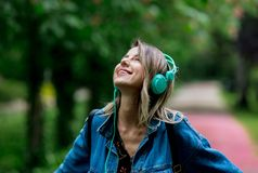 Woman with a headphones at blossom trees on background stock photos