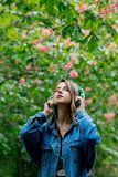 Woman with a headphones at blossom trees on background royalty free stock photos