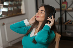 Woman with headphones on chair Royalty Free Stock Image