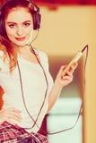 Woman with headphones choose music on smartphone. Stock Photo