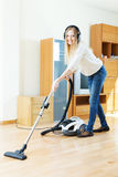 Woman in headphones cleaning with vacuum cleaner Royalty Free Stock Images