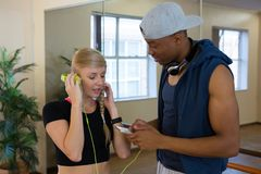 Woman with headphones connected to phone held by friend in studio. Woman with headphones connected to phone held by male friend in dance studio Stock Photos