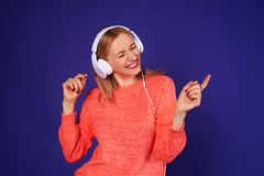 Woman in headphones dancing. Over violet background Stock Images