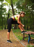 Woman with headphones doing fitness exercises in park Royalty Free Stock Image