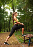 Woman with headphones doing fitness exercises in park Royalty Free Stock Photography