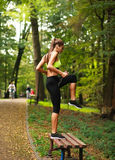 Woman with headphones doing fitness exercises in park Stock Photos