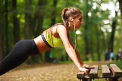 Woman with headphones doing push-ups exercises in park Royalty Free Stock Photo