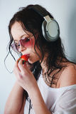 Woman in headphones eating strawberry Royalty Free Stock Photography
