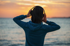 Woman in headphones enjoying sunset over the sea Stock Photo
