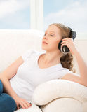 Woman in headphones enjoys music while lying on the sofa at home Royalty Free Stock Image