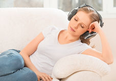 Woman in headphones enjoys music while lying on the sofa at home Stock Images