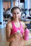 Woman with headphones in fitness gym Stock Images