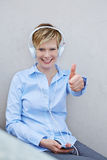 Woman with headphones holding thumbs up Royalty Free Stock Image