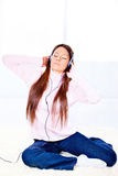 Woman with headphones at home. Pretty young woman with headphones listening music at home Royalty Free Stock Photo