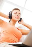 Woman with headphones and laptop at home Stock Photos