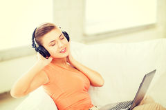 Woman with headphones and laptop at home Royalty Free Stock Image