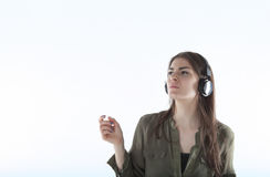 Woman with headphones listening anf enjoing music. Girl with headphones against white background isolated. Stock Images