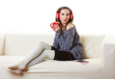 Woman with headphones listening music. People leisure relax concept. Woman casual style red big headphones listening music mp3, sitting on couch at home relaxing Stock Photography