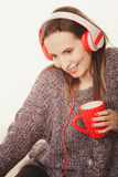Woman with headphones listening music. People leisure relax concept. Woman casual style red big headphones listening music mp3, sitting on couch at home relaxing Royalty Free Stock Image