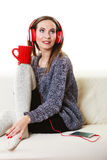 Woman with headphones listening music. People leisure relax concept. Woman casual style red big headphones listening music mp3, sitting on couch at home relaxing Royalty Free Stock Images