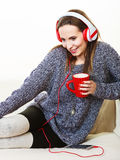 Woman with headphones listening music. People leisure relax concept. Woman casual style red big headphones listening music mp3, sitting on couch at home relaxing Royalty Free Stock Photo