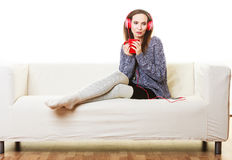 Woman with headphones listening music. People leisure relax concept. Woman casual style red big headphones listening music mp3, sitting on couch at home relaxing Stock Image